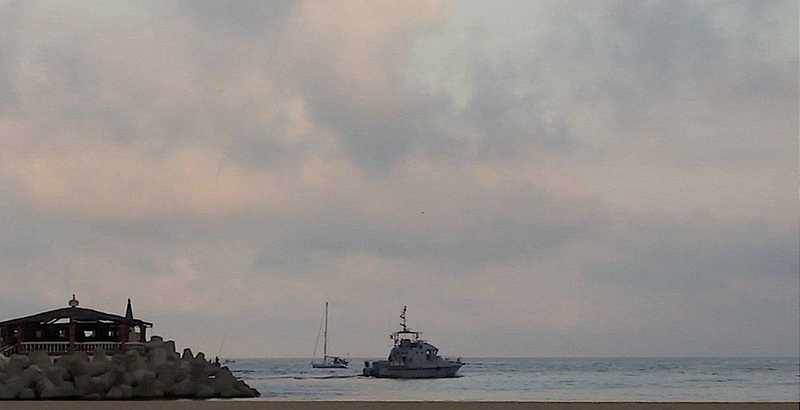 boat escorted out by marine ship.jpg